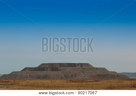 Industrial Pyramid Of Earth Extracted In The Quarry. Mountain Waste Rock In The Shape A Pyramid.