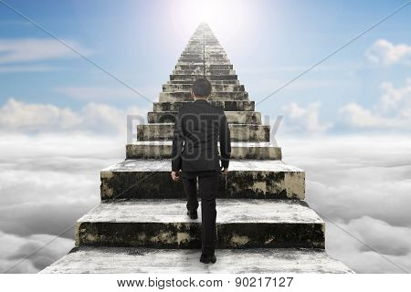 Businessman Climbing The Old Concrete Stairs With Cloudscape Sunlight
