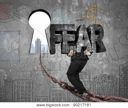 Man Carrying Fear Word On Chain Toward Keyhole With Cityscape