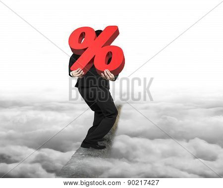 Man Carrying Red Percentage Sign On Ridge With Cloudy