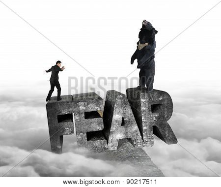 Businessman Against Bear Balancing On Fear 3D Word With Cloudy