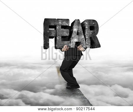 Man Carrying Fear Concrete Word On Ridge With Cloudy