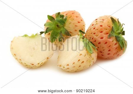 two pineapple strawberries and a cut one on a white background