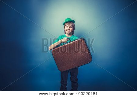 European-looking boy of  ten years in a hat holding a suitcase i