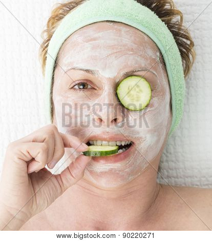 Forty year old woman with face mask and cucumber