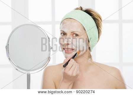 Forty year old woman putting mask on her face