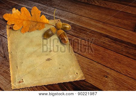 Old Grunge Paper With Autumn Oak Leaves And Acorns On The Wooden Background