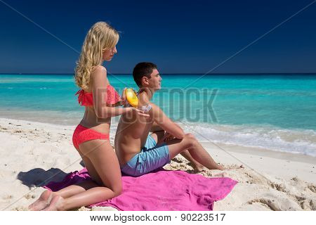 Woman Applying Heart Shape Sun Protection Lotion On Man Back