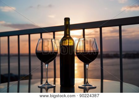 Silhouette Of Bottle And Glasses With Red Wine In Sunset