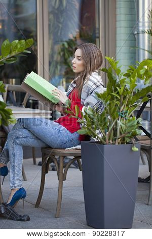Young beautiful brunette woman sitting on the street with the restaurant menu