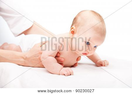 Three month baby girl is receiving back massage from a female massage therapist