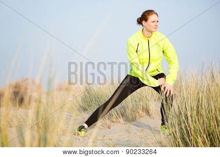 Female Runner Stretching On A Beach