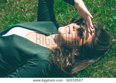 young smiling urban woman with sunglasses lie in grass looking up, retro colors