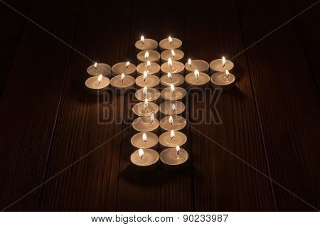 Lit tea lights in the shape of a cross on  wooden surface.