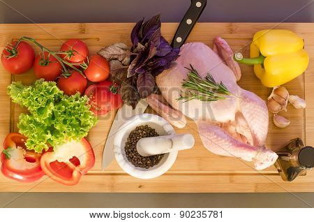 Row chicken with vegetables and spice on wooden table