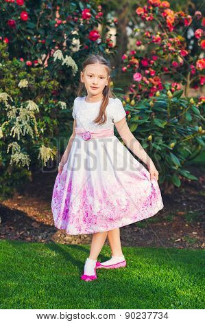 Outdoor vertical portrait of a cute little girl, wearing beautiful bridesmaid dress, toned image