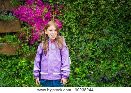 Outdoor portrait of a cute little girl under the rain