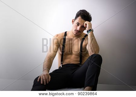 Shirtless athletic young man with suspenders sitting on floor