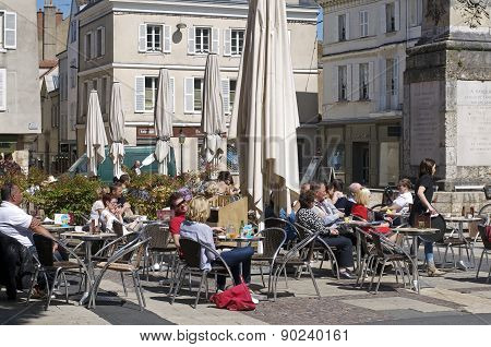 people sitting at a sidewalk cafe