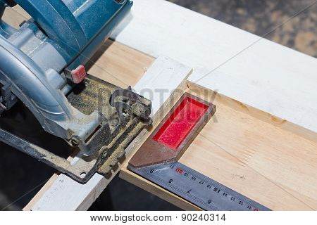 Circular Saw Cutting Wood And Iron Ruler