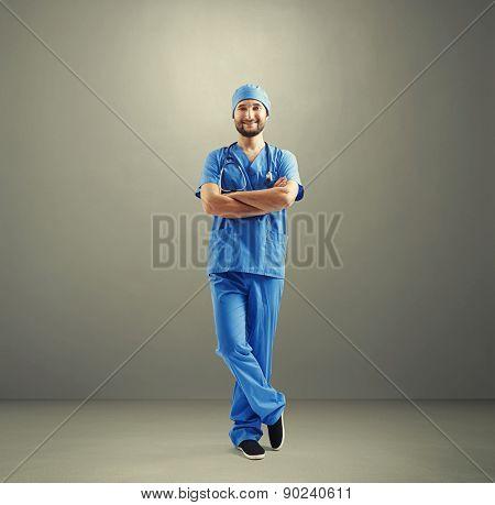 full length portrait of smiley man in blue medical uniform over grey background