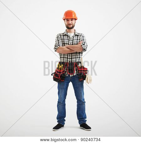 full length of confident workman with tools in orange helmet standing over light background