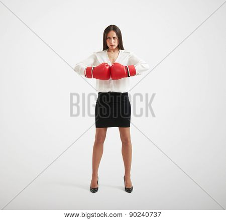 full length portrait of confident businesswoman with red gloves looking at camera over light background
