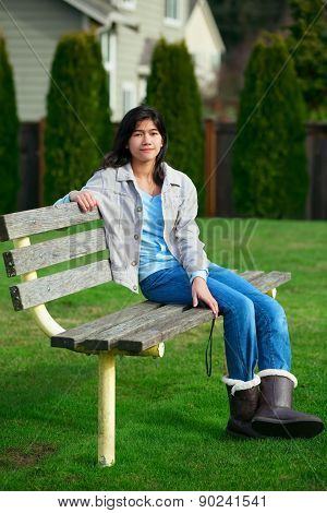 Young Biracial Teen Girl Relaxing Outdoors On Park Bench