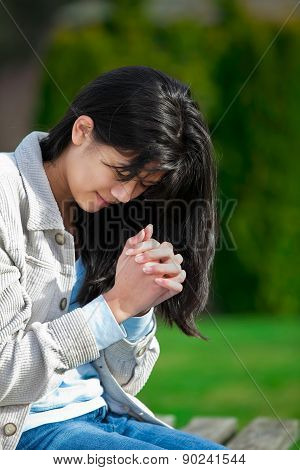 Young Biracial Teen Girl Praying Outdoors On Bench