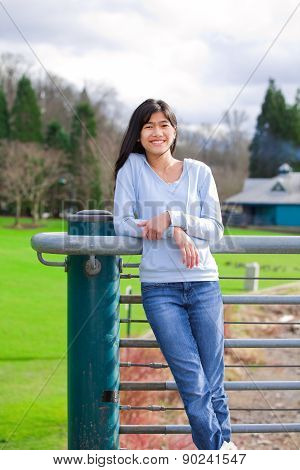 Young Teen Girl Standing, Leaning Against Railing At Park