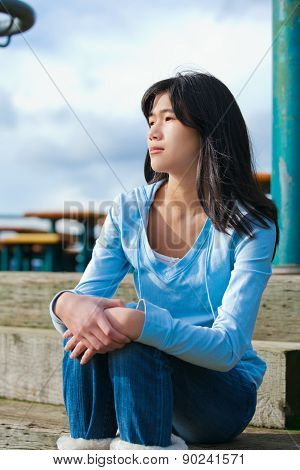Young Teen Girl Sitting On Wooden Steps Outdoors On Overcast Cloudy Day