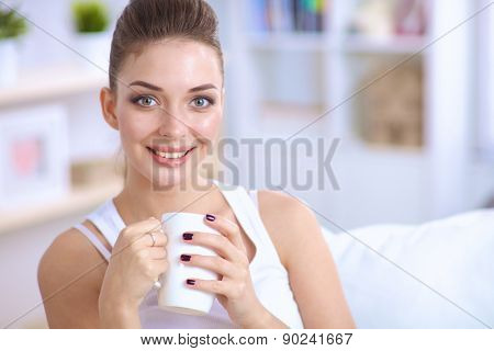 Portrait of oung beautiful woman with a cup on sofa at home.
