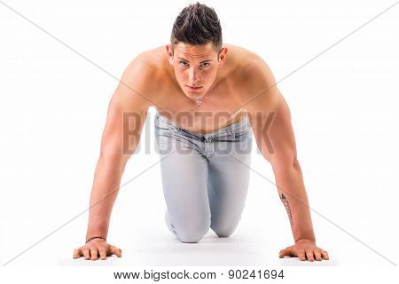 Handsome young muscular man shirtless ready to sprint and run