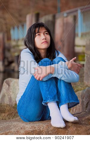Sad Teen Girl Sitting On Rocks Along Lake Shore, Lonely Expression