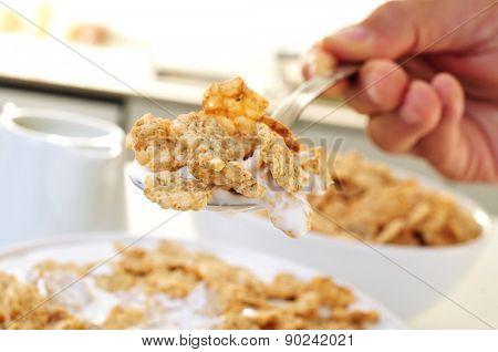 closeup of the hand of a young caucasian man with a spoon full of oatmeal cereals and yogurt for breakfast