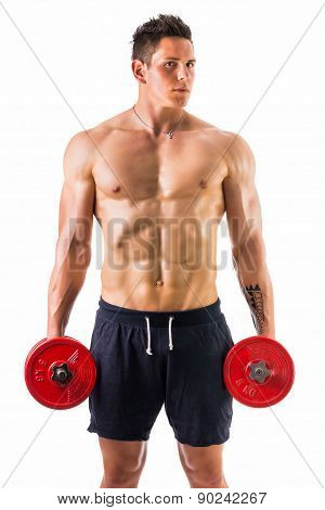 Muscular shirtless young man holding dumbbells
