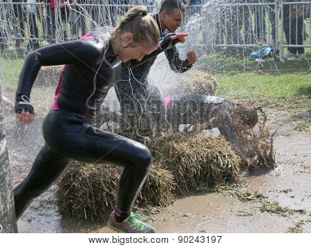 Woman And Man Running, One Woman Has Fallen In The Mud