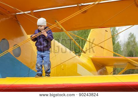 Child On The Wing Of An Airplane