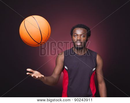Basketball player playing with a basketball on dark background
