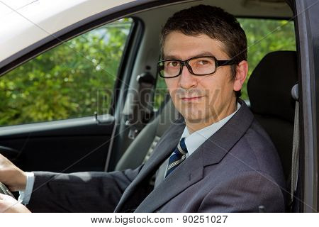 Happy businessman sitting in drivers seat in his car