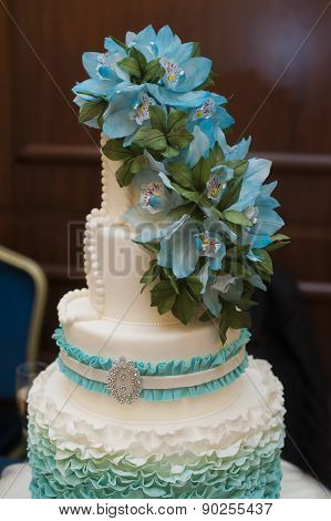 Beautiful Turquoise Three-tiered Wedding Cake With Flowers On Top