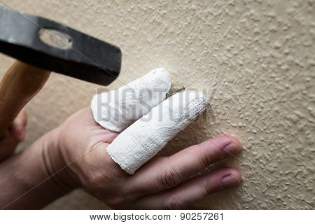 Man Is Hammering A Nail Into A Wall