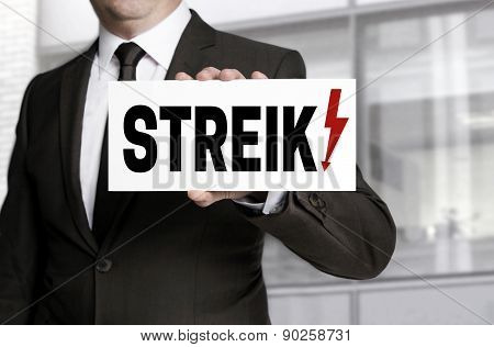 Businessman Holding Strike Sign To Viewer