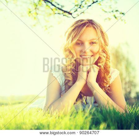 Beauty Fresh Romantic Girl lying on summer field Outdoors. Nature. Beautiful Model young Woman with long curly hair Smiling. Cute Teenage Girl lying on grass. Meadow. Grassland. Allergy free. Sunshine