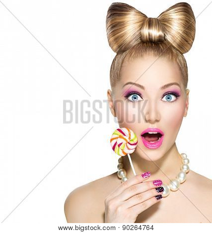 Beauty fashion model girl Eating colourful lollipop. Lollypop. Surprised Young funny woman with bow hairstyle, pink nail art and makeup isolated on white background