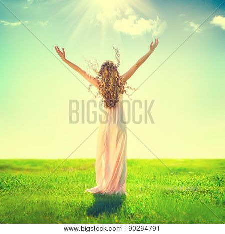 Beauty Girl enjoying nature on the field. Beautiful slim Woman Outdoor raising hands in sunlight rays. Full length Model in long dress. Grassland, Sun Light. Happy Free Lady. Health care concept