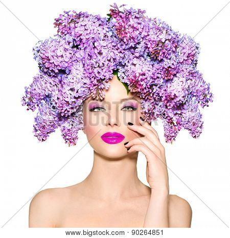 Beauty fashion model Girl with Lilac Flowers Hair Style. Beautiful Model woman with Blooming flowers on her head. Nature Hairstyle. Holiday Creative Makeover. Makeup and manicure. Make up
