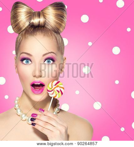 Beauty fashion model girl Eating colourful lollipop. Surprised Young funny woman with bow hairstyle, pink nail art and makeup over pink polka dots background