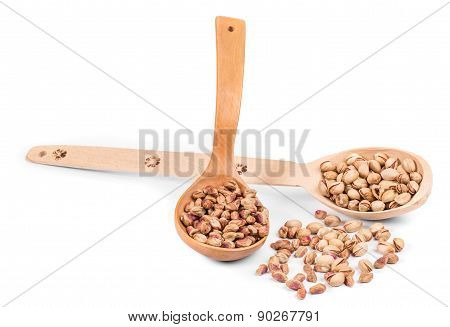 Two wooden spoons with pistachios.