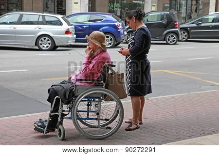 Venice, Mestre-june 29, 2014:  Young Woman Pushing A Old Woman In A Wheelchair.  Venice, Mestre-june